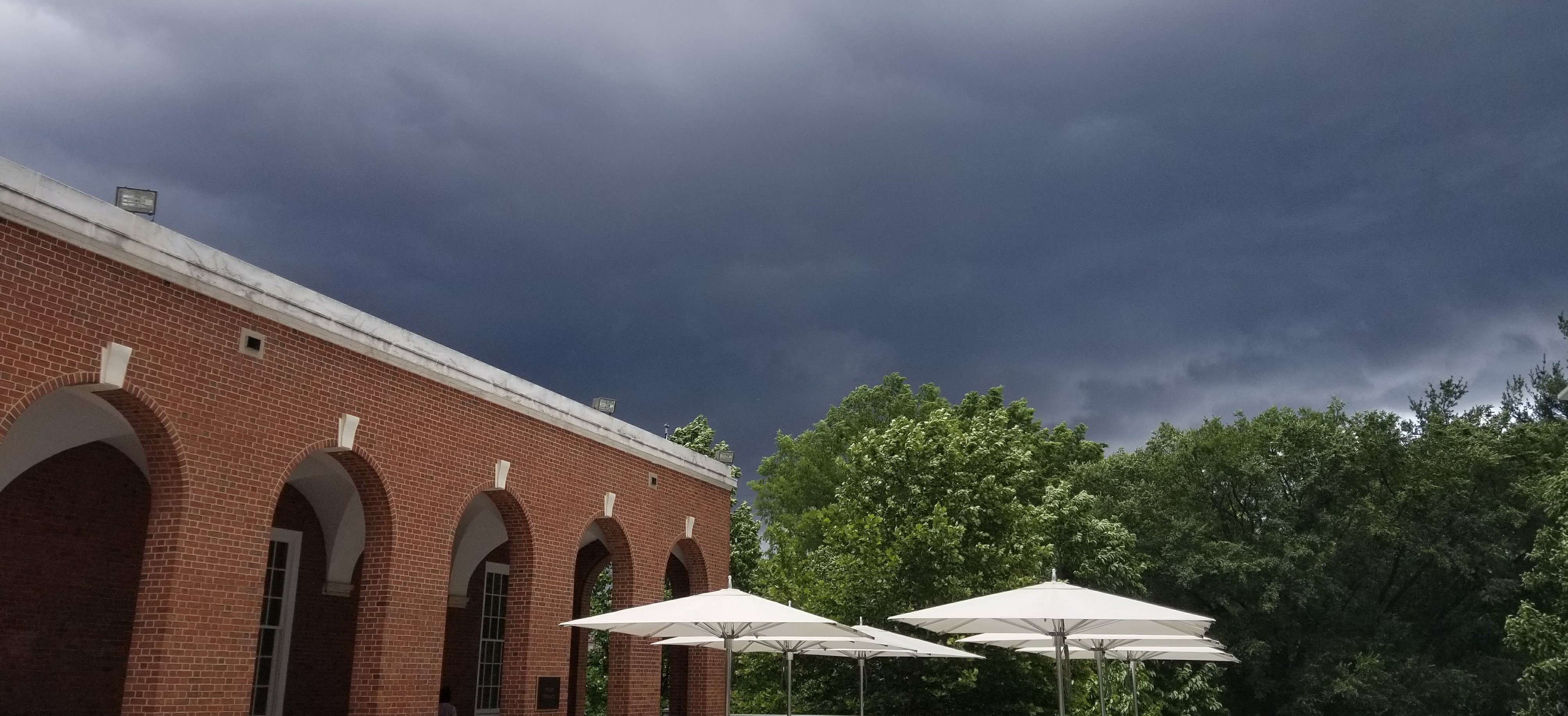 Brick archway and white umbrellas overshadowed by clouds.